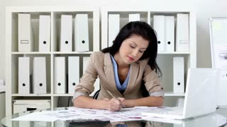 Unhappy office girl being overloaded with paperwork