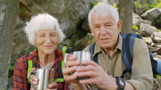 Active senior couple sitting in the forest while taking a break during hike, drinking tea from metal cups, smiling and talking at camera