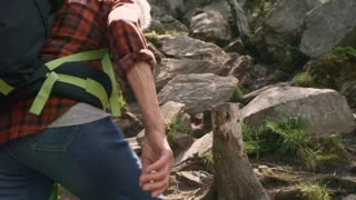 Active senior couple with backpacks hiking in mountains: man holding hands with wife while climbing steep trail