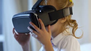 Adorable girl primary school girl wearing virtual reality glasses to learn about virtual worlds