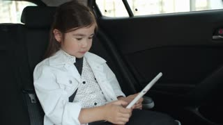 Adorable little Asian girl riding in backseat of car and playing on modern digital tablet