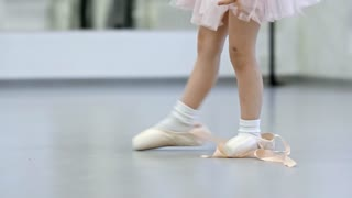Adorable little girl in pink tutu skirt and leotard trying to dance in big pointe shoes during ballet class, tilt up shot