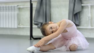 Adorable little girl learning ballet moves and doing stretching exercises when training in dance studio