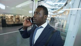 African american businessman moving down in glass elevator in large office center and talking on cell phone