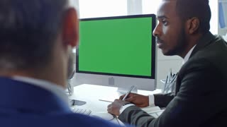 African American businessman sitting at meeting table in the office, speaking with colleagues and video calling on computer with chroma key screen