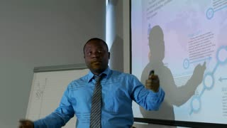 African american businessman standing at whiteboard and explaining presentation at meeting in dark office