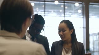 African businessman and Asian businesswoman standing at check-in desk in hotel and speaking with female receptionist; man giving passport for registration