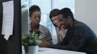 African businessman showing something on smart phone to female colleagues, they talking and smiling in office