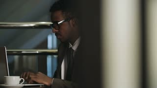 African businessman sitting at table in hotel lobby, working on laptop and drinking coffee