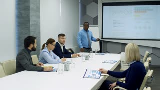 African businessman using remote and giving presentation to multi-ethnic team of colleagues at corporate meeting