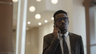 African manager walking through hotel lobby and talking on mobile phone with business partner