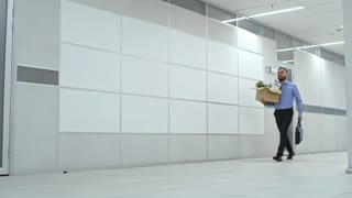 Asian businessman walking with briefcase through hallway and carrying cardboard box filled with personal belongings while moving in new office