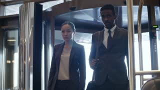 Asian businesswoman and African businessman entering hotel and walking together through lobby