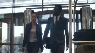Asian businesswoman and African businessman walking together through lobby in hotel and talking