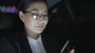 Asian businesswoman in glasses typing on mobile phone and looking out window of car driving through city at night