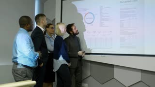 Asian entrepreneur showing presentation projected on whiteboard to multiethnic business team in dark office and explaining information on slide