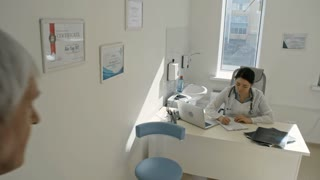 Asian female practitioner greeting senior patient in her office, examining x-ray image and writing down prescription