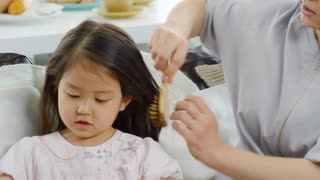Asian mother brushing long hair of cute little girl sitting on sofa and playing with toy cars