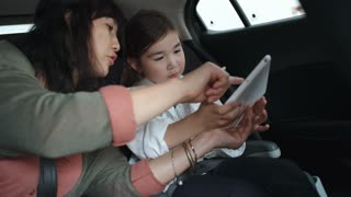 Asian woman riding with little daughter in backseat of car and showing something to girl on screen of digital tablet