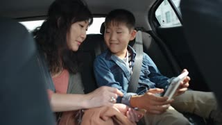Asian woman riding with little son in backseat of car and showing him how to use digital tablet