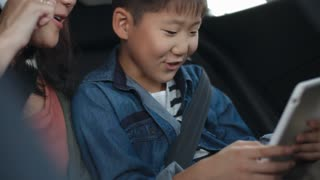 Asian woman talking on cell phone and little son playing on digital tablet while riding together in car