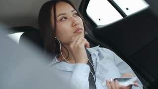 Attractive Asian woman riding in car in backseat and listening to music with headphones on smartphone
