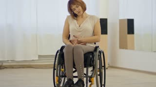 Attractive female dancer in wheelchair showing dancing moves and speaking with somebody in studio