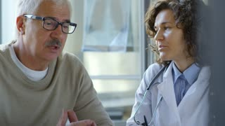 Attractive female doctor and senior man in eyeglasses speaking in clinic during medical consultation