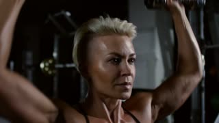 Attractive muscular woman with stylish haircut doing dumbbell shoulder press in dark gym