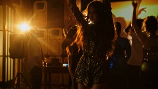 Attractive young woman in glitter dress enjoying music at party in nightclub, her friends dancing and watching video of partying people displayed on projector screen in the background