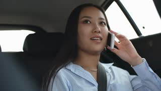 Beautiful Asian lady riding in backseat in car and talking on mobile phone