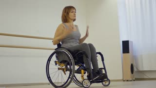 Beautiful concentrated woman learning dance moves while sitting in wheelchair in studio