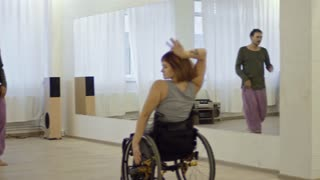 Beautiful paraplegic woman spinning around and dancing in wheelchair with male choreographer in studio