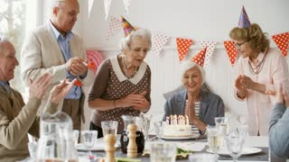 Beautiful senior woman in party hat sitting at celebration table and blowing off birthday candles on cake with help of best friends; elderly men and women clapping hands and laughing at party