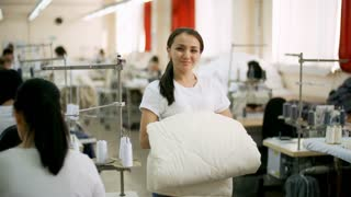 Beautiful young Asian seamstress holding white blanket, looking at camera and smiling while posing in sewing factory