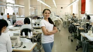 Beautiful young Asian woman standing with arms crossed, looking at camera and smiling while working in sewing factory