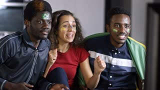 Beautiful young woman and two African-American men sitting on couch with flag and supporting Brazil team, shouting in excitement, getting joyous and embracing while celebrating goal