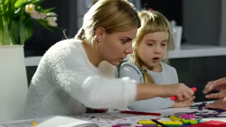 Blonde little girl doing origami with help of grandmother and drawing on paper with mom while doing crafts at home