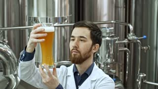 Brewery worker in lab coat drinking freshly made beer from glass while checking quality of beverage at factory