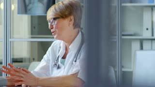 Careful female doctor sitting at table in clinic, holding hands of senior male patient and telling him news about diagnose