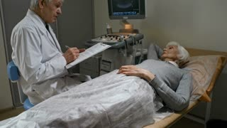 Careful senior doctor sitting by elderly female patient in hospital ward with ultrasound machine, speaking with her and writing down on clipboard