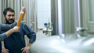 Cheerful brewery workers looking at freshly made beer in glass tube and discussing it at plant