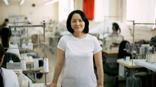 Cheerful middle-aged Asian seamstress standing by sewing machine in textile factory, looking at camera and smiling