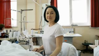 Cheerful middle-aged Asian woman sitting at workplace in textile factory with sewing machine and fabric and looking at camera