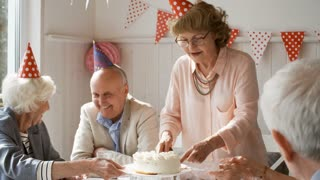 Cheerful senior men and women sitting at holiday dinner and smiling while lady in party hat serving birthday cake