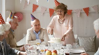 Cheerful senior woman in party hat smiling and chatting with guests while cutting birthday cake at dinner party
