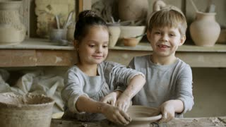 Cinemagraph of cute little sister and brother molding wet clay into pot on spinning pottery wheel in workshop