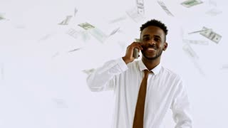 Cinemagraph of happy black businessman standing against isolated white background and using stack of money as phone; banknotes falling on him from above