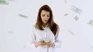 Cinemagraph of pensive beautiful woman standing against isolated white background and looking at cash money in her hands; banknotes falling on her from above