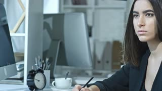 Cinemagraph of young pretty businesswoman with hair flowing in the air sitting at desk in the office, holding pen and looking at computer screen